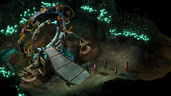 Four people approach a large wheel-like machine in a cave.