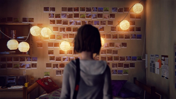 A femme looking person standing in a bedroom. Wall with lots of photos on it. Lights hang across from the ceiling.