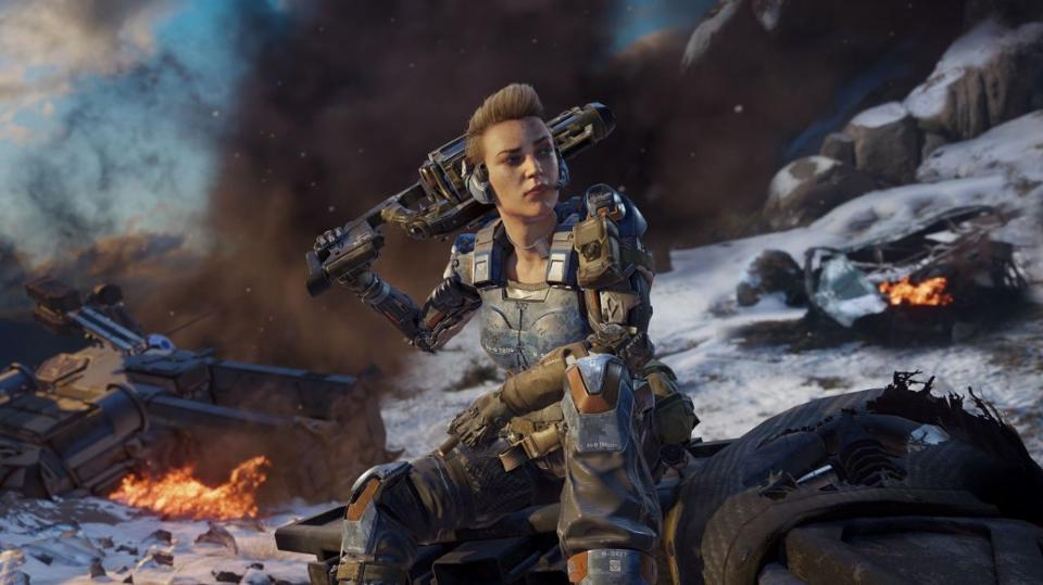 A feminine figure has a gun over her shoulder and is surrounded by fire and smoke.