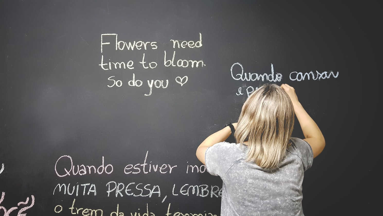 A blackboard with phrases written in different languages on it, and a child writing on it.