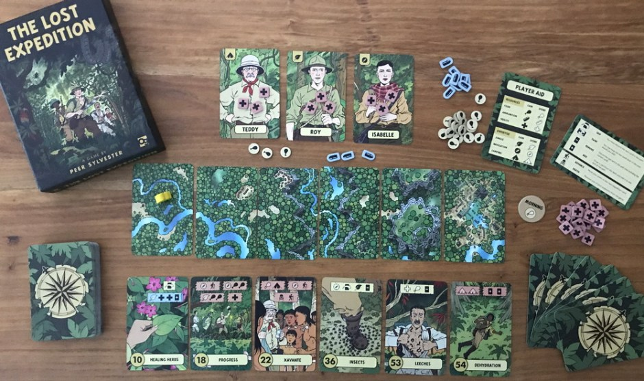 A set of cards with forest imagery on them. Three cards have people on them, and the backs of cards have compass roses on them. There are counters nearby and a book.